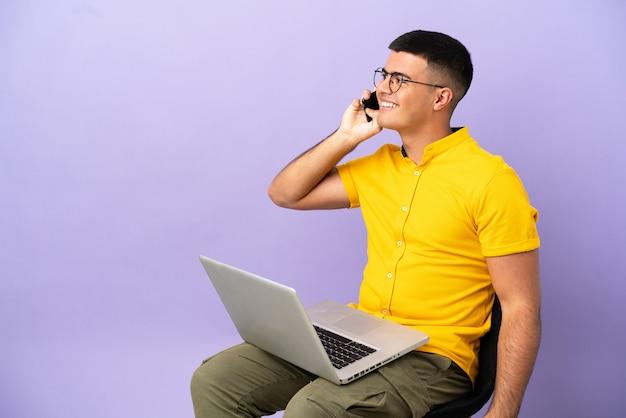 Junger mann sitzt auf einem stuhl mit laptop und führt ein gespräch mit dem handy mit jemandem