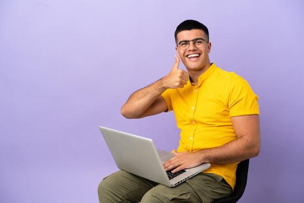 Junger mann sitzt auf einem stuhl mit laptop und gibt eine daumen-hoch-geste