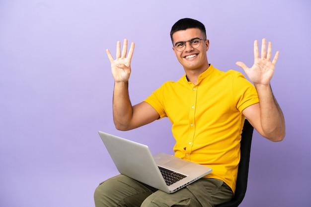 Junger mann sitzt auf einem stuhl mit laptop und zählt neun mit den fingern
