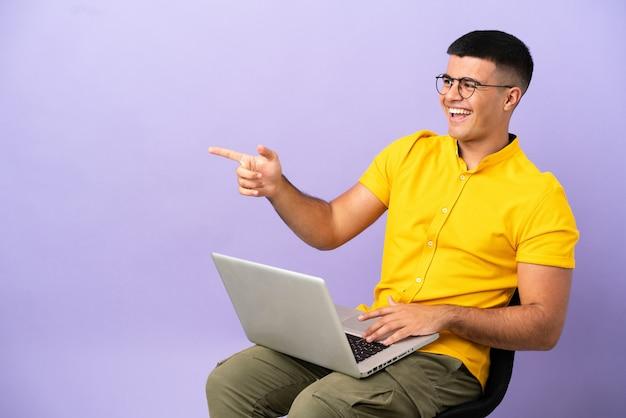 Junger mann sitzt auf einem stuhl mit laptop zeigt mit dem finger zur seite und präsentiert ein produkt