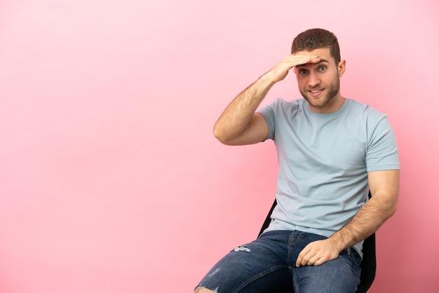 Junger mann sitzt auf einem stuhl über isoliert und schaut mit der hand weit weg, um etwas zu suchen