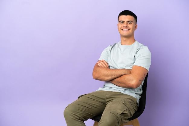 Junger mann sitzt auf einem stuhl über isoliertem hintergrund und hält die arme in frontalposition verschränkt