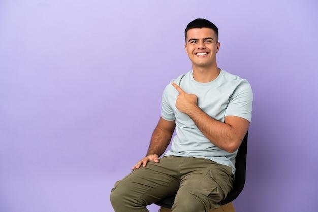 Junger mann sitzt auf einem stuhl über isoliertem hintergrund und zeigt zur seite, um ein produkt zu präsentieren