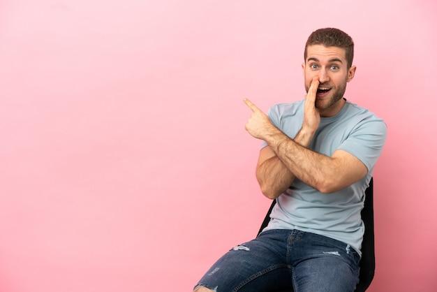 Junger mann sitzt auf einem stuhl über isoliertem rosa hintergrund, der auf die seite zeigt, um ein produkt zu präsentieren und etwas zu flüstern
