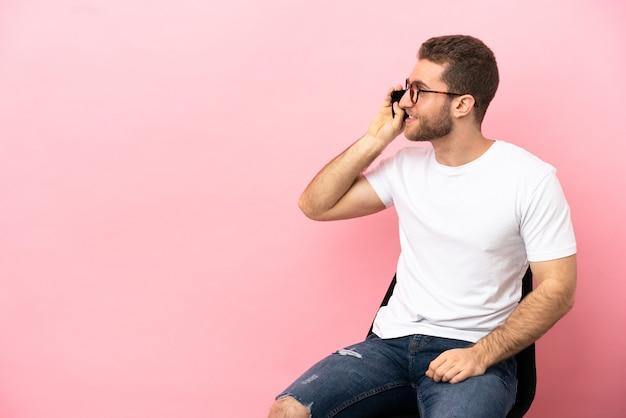 Junger mann sitzt auf einem stuhl über isoliertem rosa hintergrund und führt ein gespräch mit dem handy mit jemandem