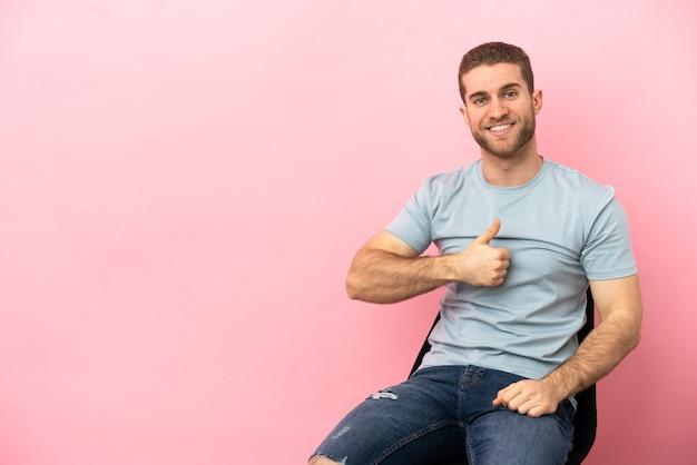 Junger mann sitzt auf einem stuhl über isoliertem rosa hintergrund und gibt eine daumen-hoch-geste