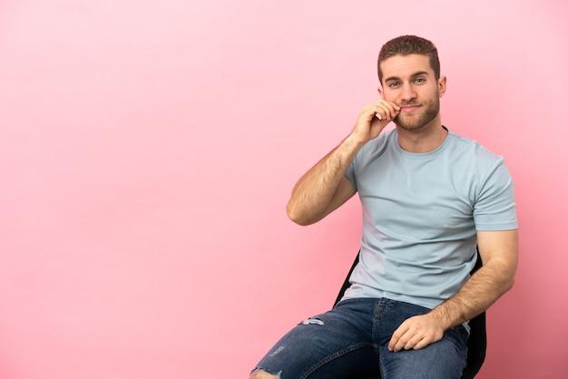 Junger mann sitzt auf einem stuhl über isoliertem rosa hintergrund und zeigt ein zeichen der stille geste