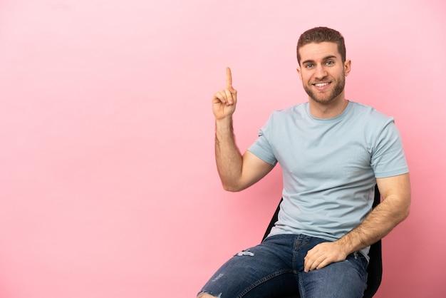 Junger mann sitzt auf einem stuhl über isoliertem rosa hintergrund und zeigt eine großartige idee