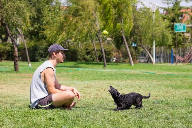 Junger mann sitzt auf gras und schwarzer hund, der tennisball in der luft betrachtet männlicher besitzer, der mit haustier spielt