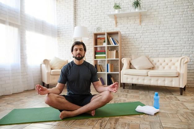 Junger mann sitzt auf mehl und meditation