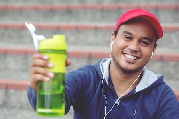 Junger mann sitzt, hört musik und bricht gerne trinkwasser, nachdem er jogging-training ausgeführt hat. durstiges gesundes männchen mit trinkwasser des passenden körpers.