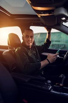 Junger mann sitzt im auto mit licht, das hinein fällt