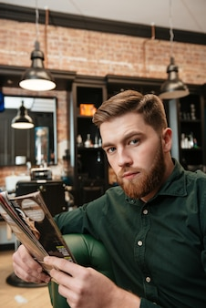 Junger mann sitzt im sessel im friseursalon und liest zeitschrift.