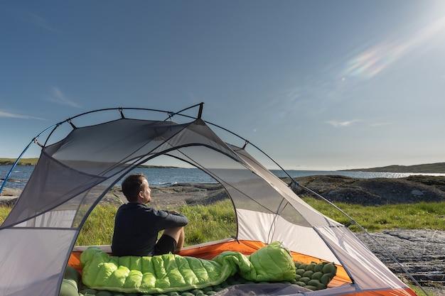 Junger mann sitzt im zelt und bewundert die strandlandschaft?