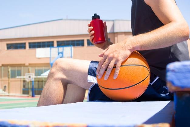 Junger mann sitzt in basketballfeld tribünen