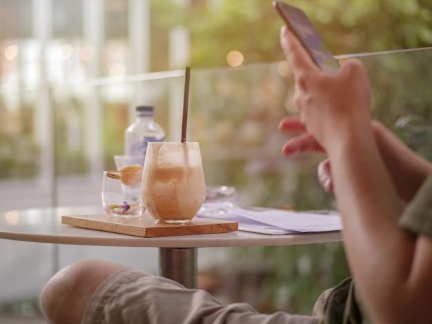 Junger mann sitzt in der kaffeestube und liest textnachricht auf dem handy.
