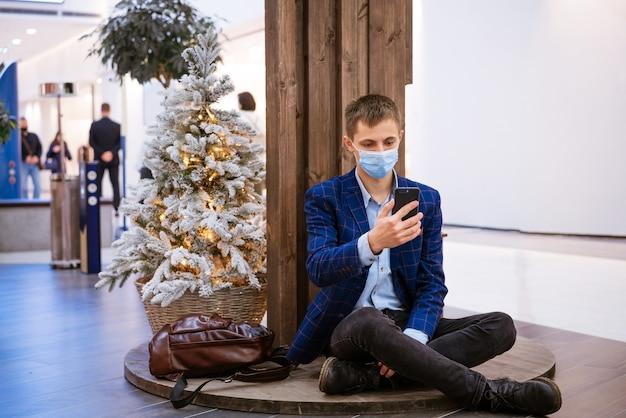 Junger mann sitzt in einem einkaufszentrum in einer medizinischen maske mit telefon in der hand am weihnachtsbaum