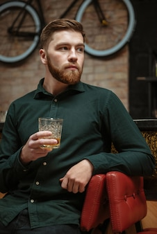 Junger mann sitzt in einem sessel und trinkt whisky