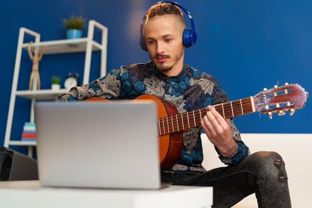 Junger mann sitzt in seinem zimmer und schaut sich das gitarren-tutorial auf dem laptop an