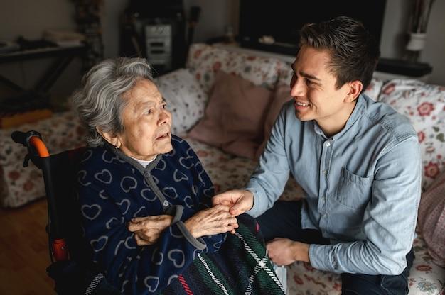 Junger mann sitzt neben einer alten kranken frau im rollstuhl und nimmt ihre hände, während er spricht und lächelt. familien-, pflegekonzept.