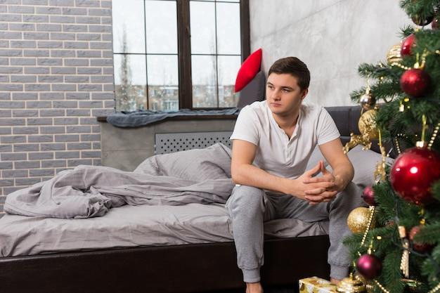 Junger mann sitzt traurig auf dem bett, frau liegt im bett und bedeckte sich mit einer decke im hintergrund, in der nähe des weihnachtsbaums