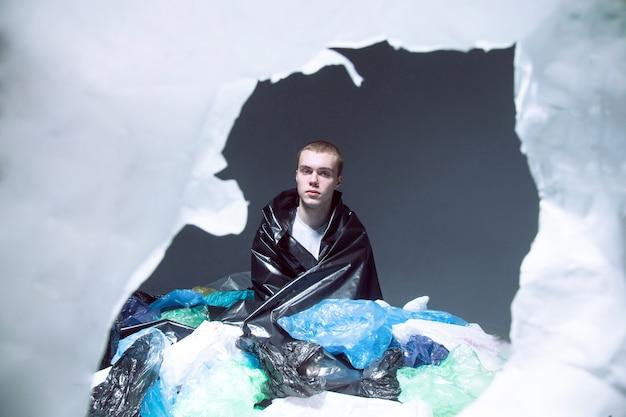 Junger mann sitzt und bedeckt mit plastiktütenmüll, dunkler heller hintergrund.