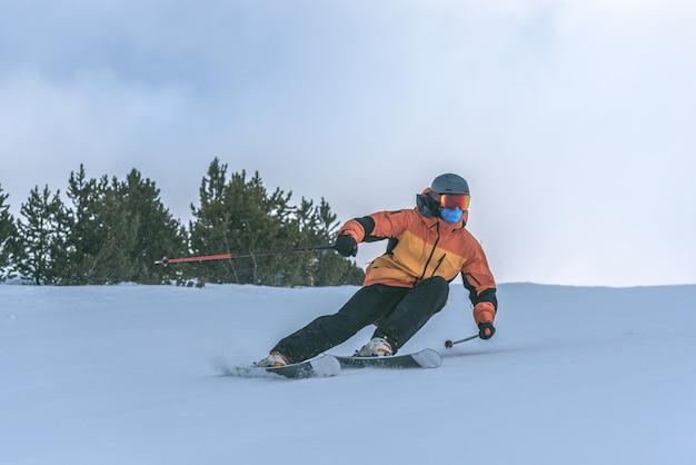 Junger mann skifahren in den pyrenäen im skigebiet grandvalira