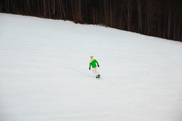 Junger mann snowboarder auf den pisten frostigen wintertag