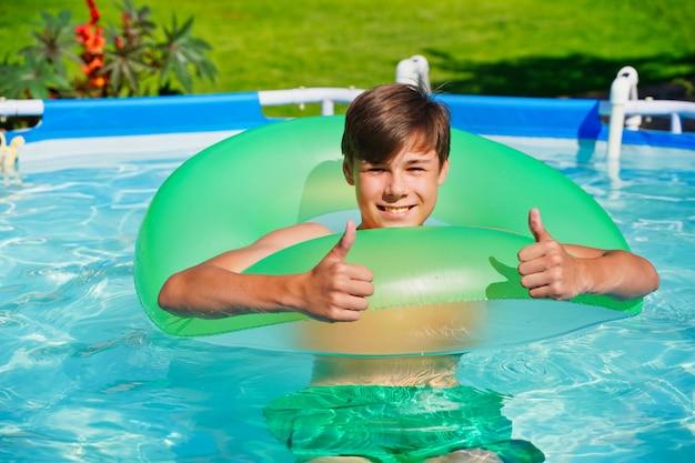Junger mann spielt aktive spiele im pool daumen hoch empfehlen sommerspaß und unterhaltung teenager s ...