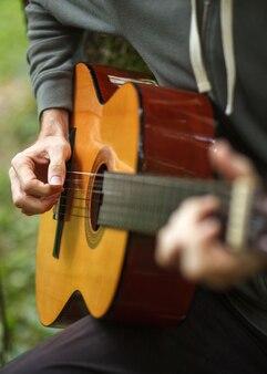 Junger mann spielt akustische gitarre auf natur im wald