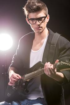 Junger mann spielt gitarre in der dunkelkammer.