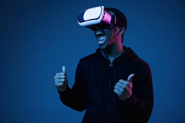 Junger mann spielt in vr-brille im neonlicht auf gradient
