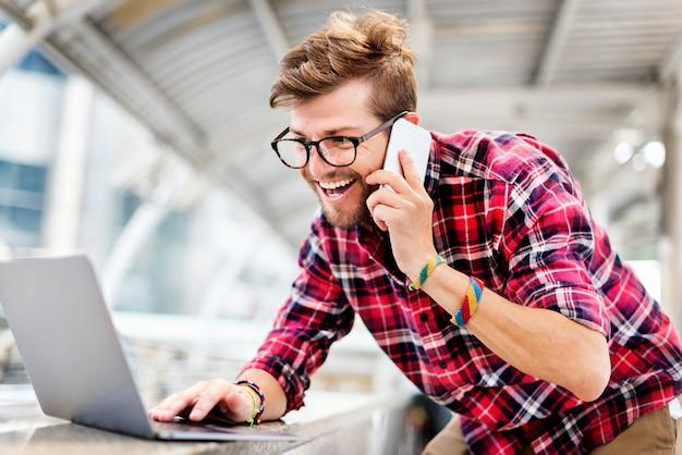 Junger mann spricht smartphone durchsuchen laptop-konzept