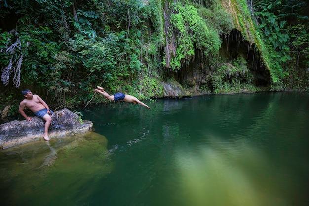 Junger mann springt klippe in sauberes wasser in wildem wasserfall versteckt in grüner sommernatur
