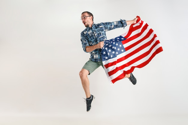 Junger mann springt mit flagge der vereinigten staaten von amerika lokalisiert auf weißem studio.