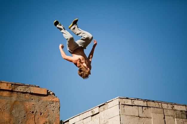 Junger mann springt und übt parkour zwischen zwei gebäuden außerhalb an klarem sommertag