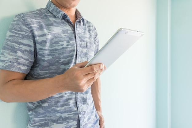 Junger mann stand in der nähe der wand und hält tablet smartphone
