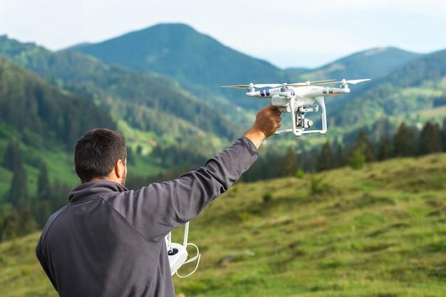 Junger mann startet einen quadrocopter am himmel auf die natur in den bergen