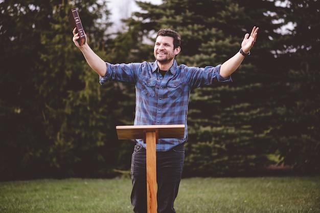 Junger mann stehend und hält die bibel in seinen händen