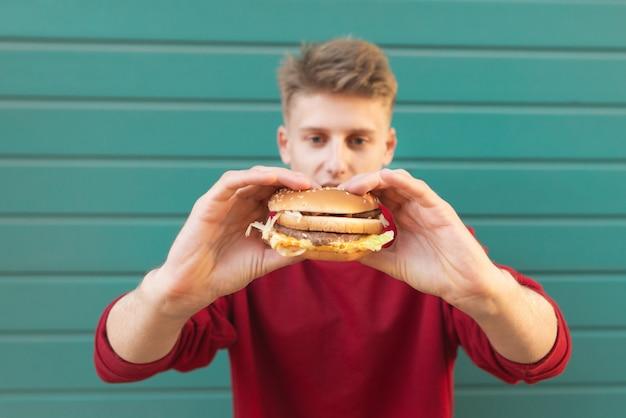 Junger mann steht auf türkis und hält einen appetitlichen burger in den händen.