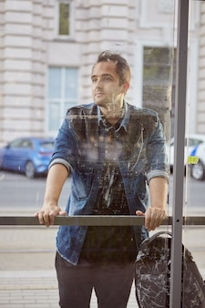 Junger mann steht hinter fenster der öffentlichen verkehrsstation.