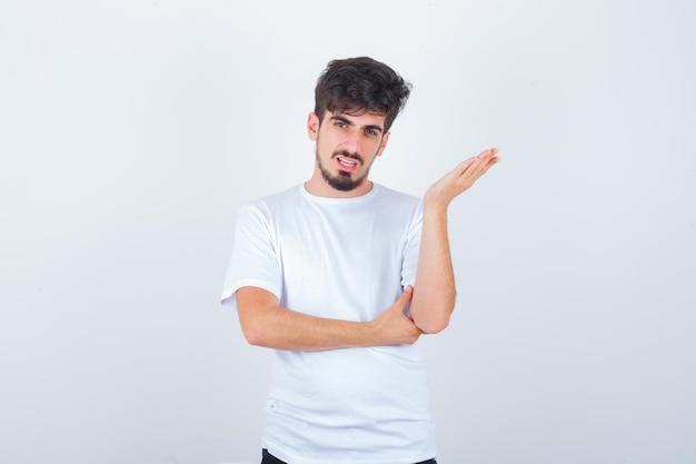 Junger mann steht in fragender pose im t-shirt und sieht selbstbewusst aus looking