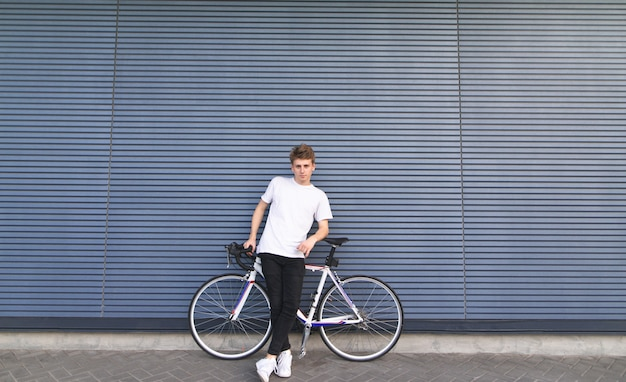 Junger mann steht mit einem weißen straßenfahrrad auf dem hintergrund der wand