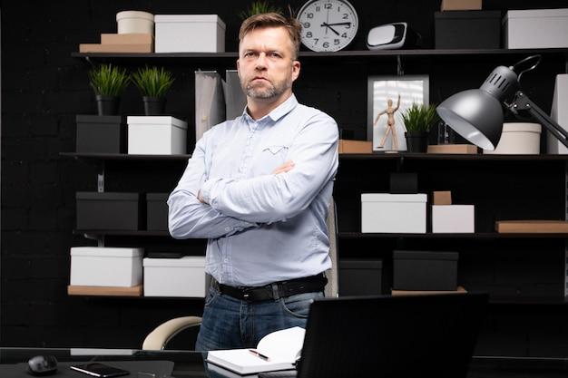 Junger mann steht neben dem computertisch und faltete die hände auf der brust