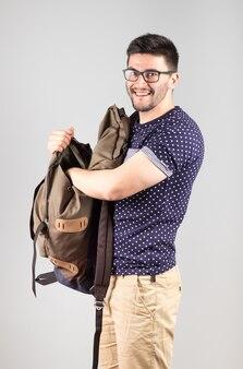 Junger mann steht und holt etwas aus seinem rucksack