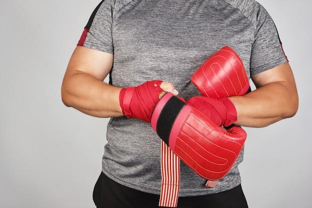 Junger mann steht und zieht seine hände rote boxhandschuhe an