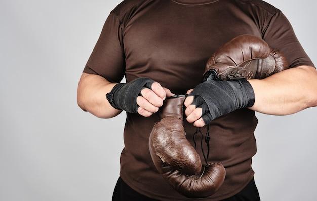 Junger mann steht und zieht seine hände sehr alte vintage braune boxhandschuhe