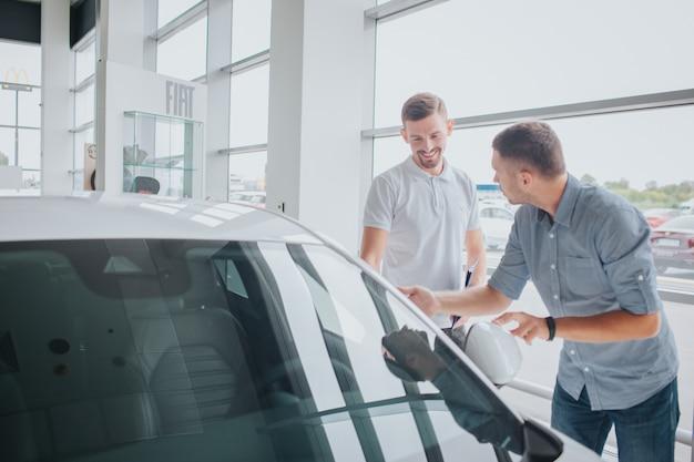 Junger mann steht vor weißem auto