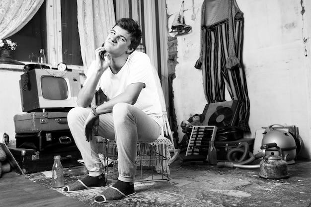 Junger mann sticht seinen pickel ins gesicht, während er im verlassenen zimmer sitzt. aufgenommen im monochrom-stil.