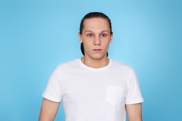Junger mann stirnrunzelnd auf blauem hintergrund isoliert. menschliche emotionen, mimik
